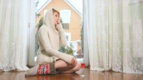 Красивая женщина в свитере сидит на поле около окна говоря телефоном акции видеоматериалы