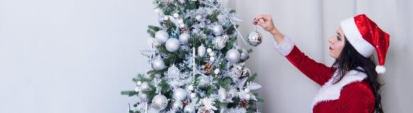 Красивая женщина в сексуальном костюме Санта Клауса украшает украшения рождественской елки дома Девушка висит серебряный шарик на стоковые фото