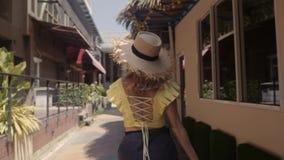 Красивая женщина в соломенной шляпе идет улица Игра к камере акции видеоматериалы