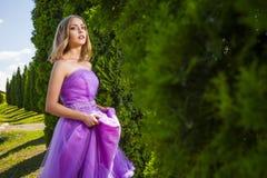 Красивая женщина в фиолетовом платье смотря камеру Стоковое Фото