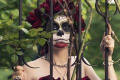 Красивая женщина в черепе сахара Calavera мексиканца макияжа традиционном на предпосылке загородки утюга с шипами день мертвый стоковые фотографии rf