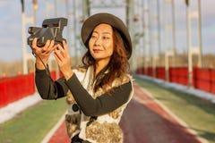 Красивая женщина в черной шляпе делает поляроидное selfie на мосте в зиме в Европе стоковая фотография rf