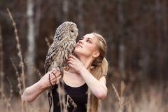 Красивая женщина в черном платье с сычом на его руке Блондинка с длинными волосами в природе держа сыча Романтичная чувствительна стоковое изображение