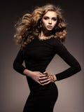 Красивая женщина в черном платье bodycon с длинным вьющиеся волосы стоковая фотография rf
