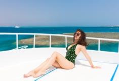 Красивая женщина в черно-зеленом купальнике лежа на палубе th Стоковая Фотография