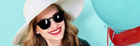Красивая женщина в шляпе и солнечных очках лета держа воздушные шары Привлекательный холодный портрет моды молодой женщины стоковое фото