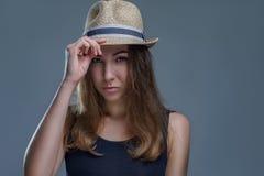 Красивая женщина в шляпе и черной рубашке представляющ стильно изолирует на серой предпосылке в конце студии вверх стоковая фотография