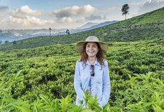 Красивая женщина в шляпе усмехаясь пока стоящ на плантации чая стоковое фото rf