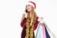 Красивая женщина в шляпе santa, с сумками рождества в руке, talki стоковая фотография
