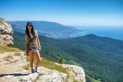 Красивая женщина в шортах стоя на скале с красивым видом, концепцией туризма и перемещением стоковая фотография rf