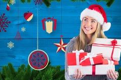 Красивая женщина в шляпе santa держащ подарки против цифров произведенной предпосылки Стоковое фото RF