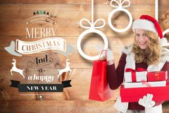 Красивая женщина в шляпе santa держа подарки и хозяйственные сумки рождества Стоковые Изображения RF
