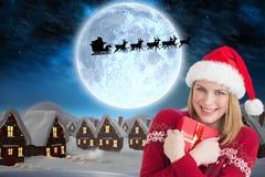 Красивая женщина в шляпе santa держа подарок рождества Стоковые Фотографии RF