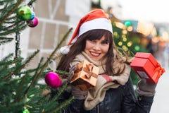Красивая женщина в шляпе santa держа 2 присутствующих коробки на chris Стоковые Изображения