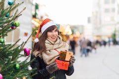 Красивая женщина в шляпе santa держа 2 присутствующих коробки на chris Стоковая Фотография RF