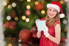 Красивая женщина в шляпе santa показывая подарок рождества Стоковые Изображения