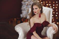 Красивая женщина в элегантном внешнем платье представляя самостоятельно, сидящ в стуле Стоковая Фотография