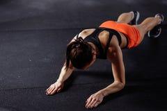 Красивая женщина в sportswear делая планку пока trainnig на спортзале креста подходящем стоковая фотография