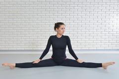 Красивая женщина в sportswear работая на студии фитнеса, выполняя шпагат сидя на поле стоковая фотография rf