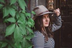 Красивая женщина в striped рубашке держа ее шляпу и смотря камеру стоковое изображение