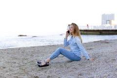 Красивая женщина говорит на черни с улыбкой и сидит на пляже n Стоковые Фотографии RF