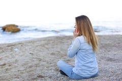 Красивая женщина говорит на черни с улыбкой и сидит на пляже n Стоковое Изображение