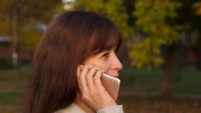 Красивая женщина говоря на смартфоне и идет в парк, счастливые улыбки девушки бизнес-леди носит черный портфель с акции видеоматериалы