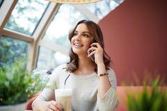 Красивая женщина говоря на черни на кафе Стоковые Фотографии RF