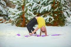Красивая женщина делая йогу outdoors в снеге Стоковые Фото