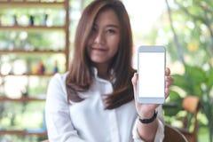 Красивая женщина держа и показывая белый мобильный телефон с пустой белой стороной экрана и smiley в кафе Стоковая Фотография