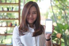 Красивая женщина держа и показывая белый мобильный телефон с пустой белой стороной экрана и smiley в кафе Стоковые Фотографии RF