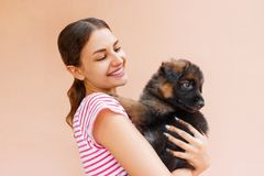 Красивая женщина держа и смотря в черное ` s щенка наблюдает стоковое фото rf