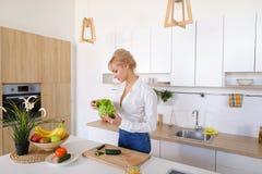 Красивая женщина домохозяйки держа зеленые лист и усмехаться салата Стоковое Фото