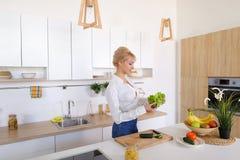 Красивая женщина домохозяйки держа зеленые лист и усмехаться салата Стоковое Изображение RF