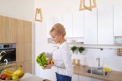 Красивая женщина домохозяйки держа зеленые лист и усмехаться салата Стоковые Фото