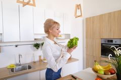 Красивая женщина домохозяйки держа зеленые лист и усмехаться салата Стоковые Фотографии RF