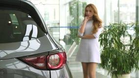 Красивая женщина думая пока выбирающ новый автомобиль на дилерских полномочиях стоковое изображение