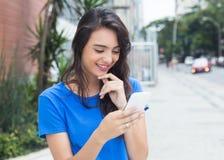Красивая женщина девушки с сообщением голубой рубашки печатая на телефоне Стоковое Изображение RF