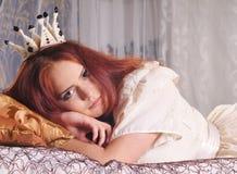 Красивая женщина лежа как prencess и смотря камеру Стоковое Фото