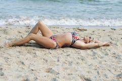 Красивая женщина лежит на песке морем Стоковое Изображение