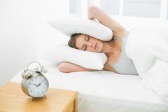 Красивая женщина держа ее уши закрыла путем использование подушки пока лежащ в ее кровати Стоковое Фото