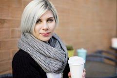 Красивая женщина держа кофейную чашку на кафе тротуара Стоковые Изображения RF