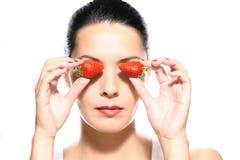 Красивая женщина держа клубники к ее глазам Стоковая Фотография