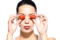 Красивая женщина держа клубники к ее глазам Стоковые Изображения