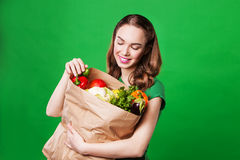Красивая женщина держа продуктовую сумку полный свежей и здоровой еды На зеленой предпосылке Стоковые Изображения RF