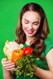 Красивая женщина держа продуктовую сумку полный свежей и здоровой еды На зеленой предпосылке Стоковые Изображения