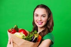 Красивая женщина держа продуктовую сумку полный свежей и здоровой еды На зеленой предпосылке Стоковое Изображение RF