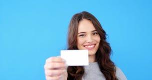 Красивая женщина держа пустую карточку посещения на голубой предпосылке сток-видео