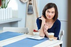 Красивая женщина есть десерт и выпивая latte кофе в кафе Стоковое Изображение