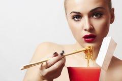 Красивая женщина есть китайскую еду. вок. конец-вверх. красные губы стоковые изображения